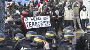 """BRU13 CALAIS (FRANCIA) 29/02/2016.- Miembros de la policía antidisturbios francesa permancen delante de un grupo de refugiados al inicio del desmantelamiento de parte del campo de inmigrantes, conocido como """"la jungla"""", en Calais (Francia) hoy, 29 de febrero de 2016. La Prefectura (delegación del Gobierno) confirmó que se ha comenzado a desalojar el campo, conocido como """"la jungla"""", y señaló que se propone una solución alternativa de realojo a cada uno de sus ocupantes. EFE/Laurent Dubrule"""